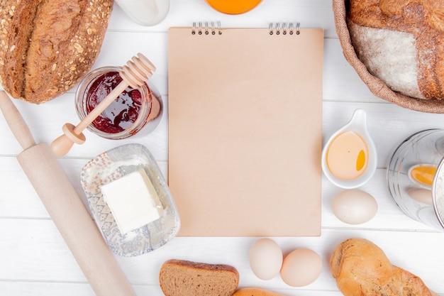 Widok z góry pieczywa z nasionami i wietnamskiego chleba żytniego i bagietki kolby z masłem jaja dżem truskawkowy wałek do ciasta i notes na drewnianym tle z miejsca na kopię