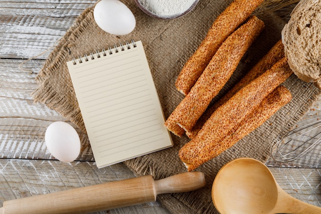 Widok z góry piekarnia z notatnika, jaja, wałek do ciasta na worek i powierzchni drewnianych. poziomy
