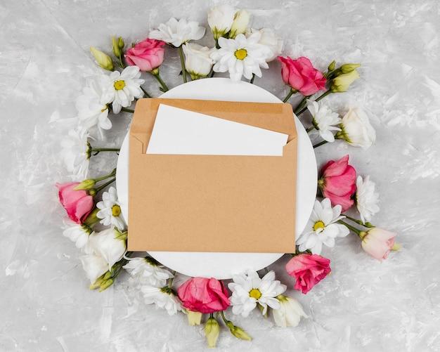 Widok z góry piękna kompozycja wiosennych kwiatów z okrągłą kartą i kopertą