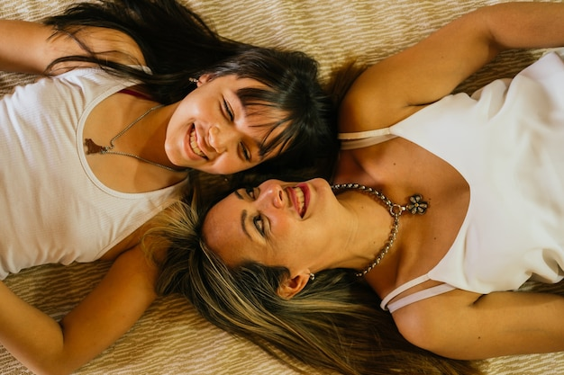 Widok z góry piękna młoda matka i jej nastoletnia córka uśmiecha się do łóżka.