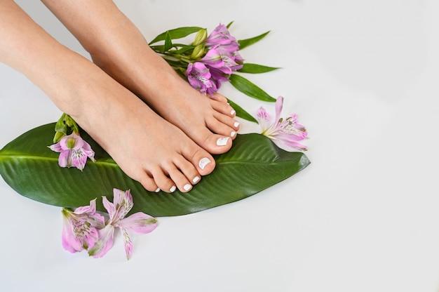 Widok z góry piękne idealne kobiece nogi nogi tropikalnych kwiatów i zielonych liści palmowych