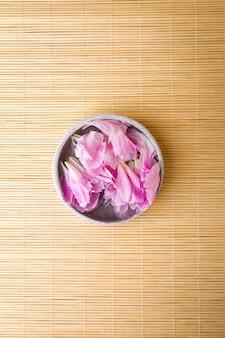 Widok z góry piękne rose flower płatków w wodzie w małych bowl na drewnianym tle azjatyckich. koncepcja spa. selektywne fokus.