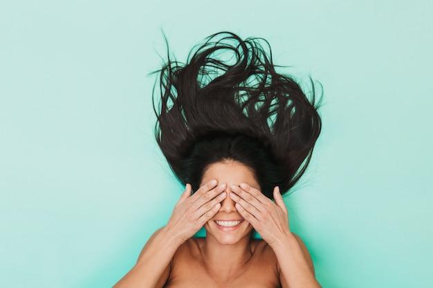 Widok z góry pięknej młodej kobiety topless brunetka z długimi włosami r. na niebiesko