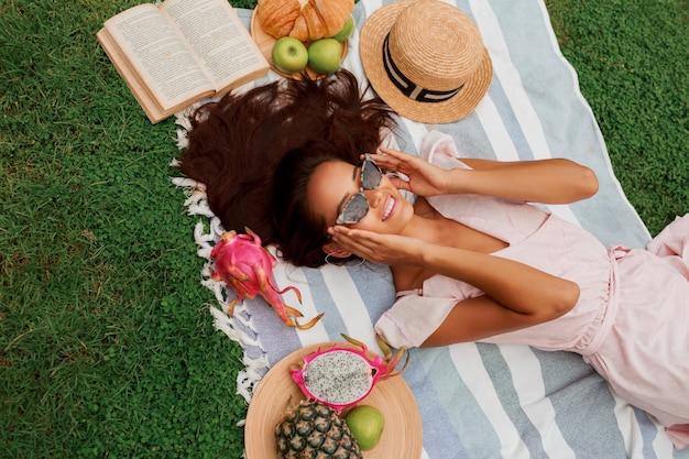 Widok z góry pięknej romantycznej kobiety w sukience leżącej na zielonej trawie.
