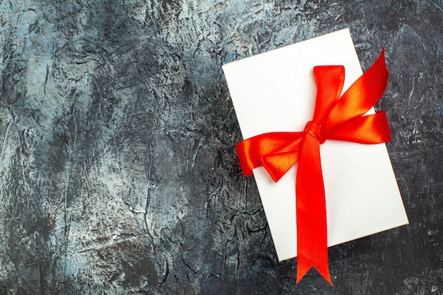 Widok z góry pięknie zapakowanych pudełek na prezenty przewiązanych czerwoną wstążką po lewej stronie na ciemnym