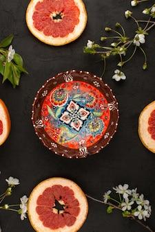 Widok z góry pierścienie grejpfruta wraz z białymi kwiatami i zaprojektowany talerz na ciemnym biurku