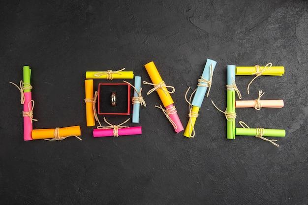 Widok z góry pierścionek zaręczynowy w pudełku miłość napisany z przewijanymi papierami życzeń na stole