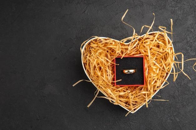 Widok z góry pierścionek zaręczynowy w pudełku w pudełku w kształcie serca na wolnym miejscu na stole