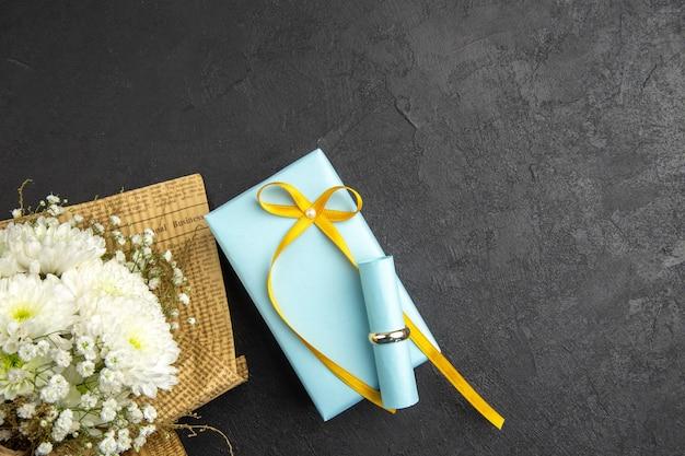 Widok z góry pierścionek zaręczynowy zwój papier życzeń na prezent bukiet kwiatów na ciemnym tle wolna przestrzeń