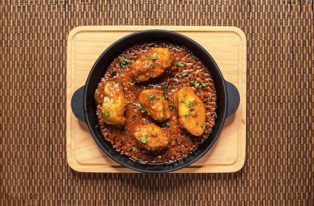 Widok z góry pikantnego i gorącego bengalskiego curry rybnego. indyjskie jedzenie. curry rybne z czerwonym chili, liściem curry, mlekiem kokosowym. kuchnia azjatycka.