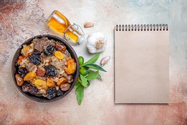 Widok z góry pilaw pilaw w misce butelka oleju owoce cytrusowe czosnek krem notebook