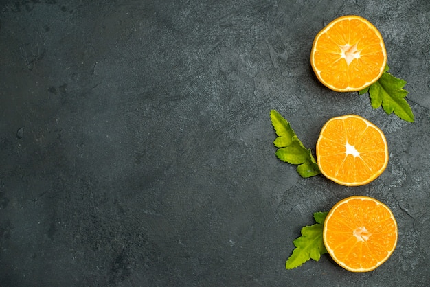 Widok z góry pionowy rząd wyciętych pomarańczy na ciemnym tle wolnej przestrzeni