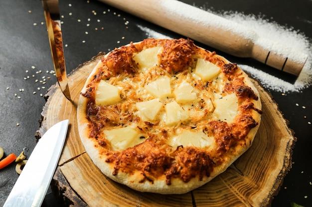 Widok z góry pizza ananasowa na stojaku z nożami wałkiem do ciasta i mąką na czarnym stole
