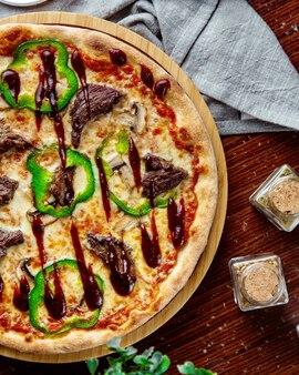 Widok z góry pizza mięso z papryką i sosem barbecue na tacy