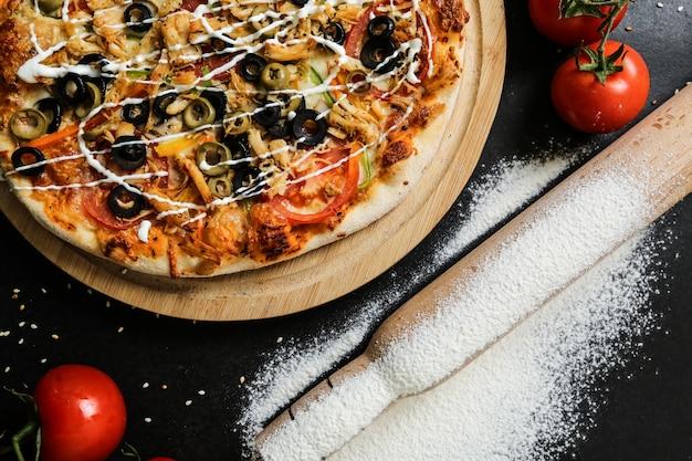 Widok z góry pizza na stojaku z pomidorami, oliwkami, wałkiem do ciasta i mąką na czarnym stole
