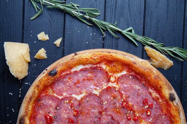 Widok z góry pizza z salami, papryczka chili, szynka i ser na ciemnym tle drewniane. skopiuj sapce do projektu. tło żywności kuchnia włoska. płaskie jedzenie