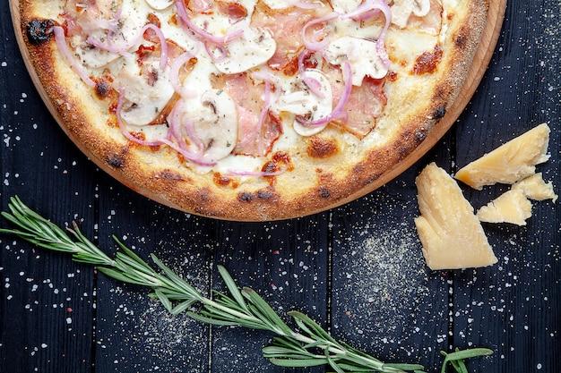 Widok z góry pizza z szynką, grzybami i parmezanem serowym na ciemnym tle drewniane. skopiuj sapce do projektu. tło żywności kuchnia włoska. płaskie jedzenie