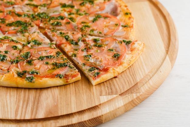 Widok z góry pizzy pokrojony na 8 kawałków i jedną przesuniętą do przodu