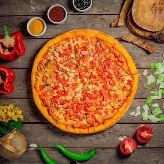 Widok z góry pizzy z posiekanymi warzywami, pieczarkami i kiełbaskami