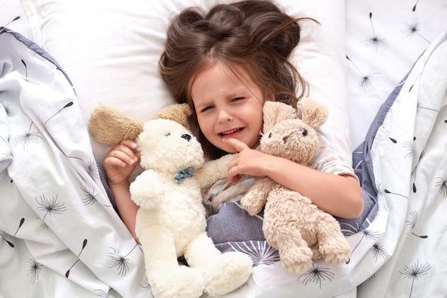 Widok z góry płaczącego dziecka w łóżku, smutne dziecko na poduszce w sypialni, mała dziewczynka leżąca na pościeli z mniszkiem lekarskim