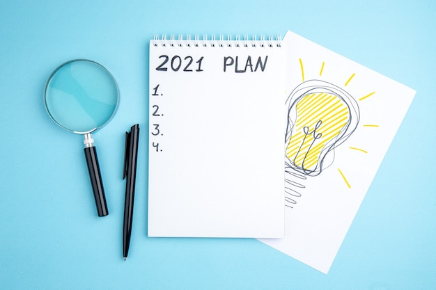 Widok z góry plan napisany na spiralnym notatniku lupa długopis pomysł na biznes żarówka rysunek na papierze na niebieskim tle
