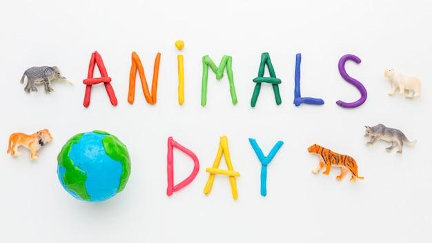 Widok z góry planety ziemi z figurkami zwierząt i kolorowym napisem na dzień zwierząt