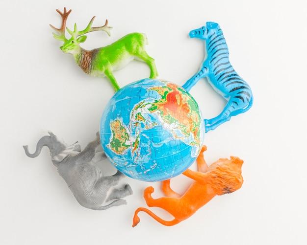 Widok z góry planety ziemi z figurkami zwierząt na dzień zwierząt