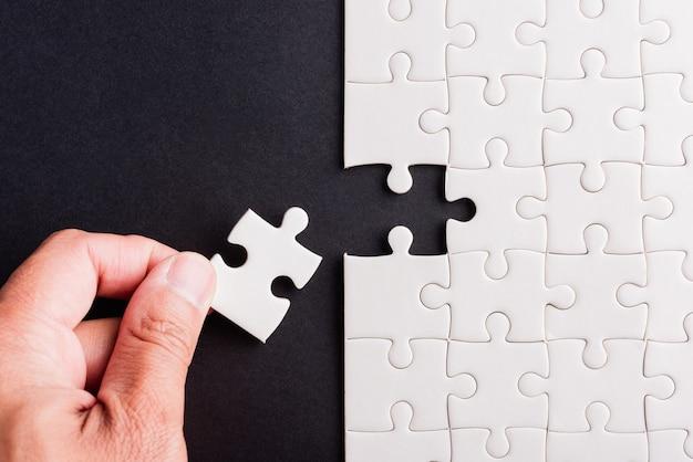 Widok z góry płaski układ trzymania ręki ostatni kawałek układanka z białego papieru ostatnie elementy ułożone w celu rozwiązania problemu zakończonej misji