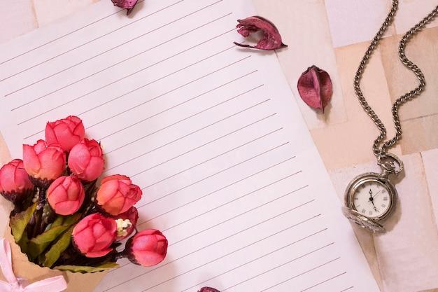 Widok z góry płaskiego strzału koperty listowej i zegarka kieszonkowego z płatkami kwiatów