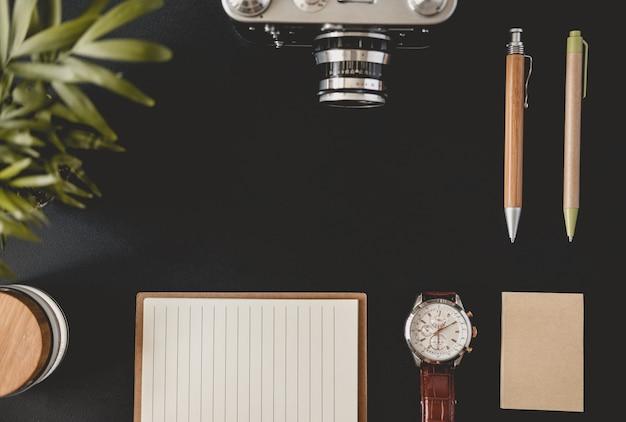 Widok z góry płaskiej strony z notatkami do pisania dwóch długopisów do oglądania słoika z kamerą filmową z drewnianą pokrywą i papierem do nagrywania leżącym na czarnym stole. koncepcja obszaru roboczego blogera lub studenta. przestrzeń reklamowa