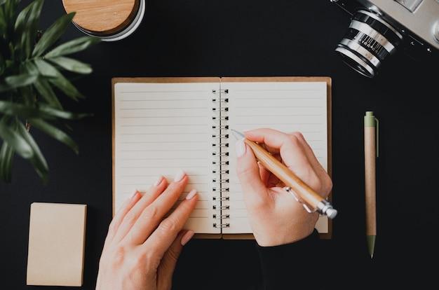 Widok z góry płaskiej świeckiej ręki womans pisze notatkę w otwartym notatniku leżącym na czarnym stole obok aparatu z długopisem i papierem do pisania. pojęcie księgowości domowej. przestrzeń reklamowa