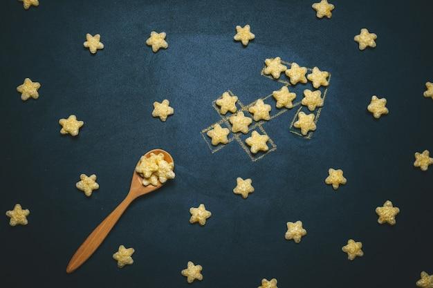 Widok z góry płasko leżącego strzelca, znak horoskopu wykonany z chrupiących gwiazd kukurydzy na czarnym tle