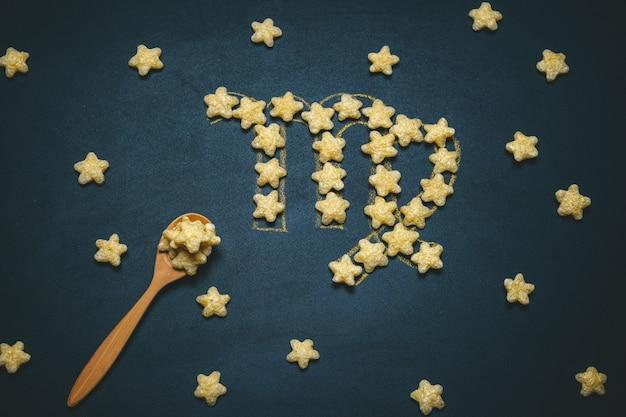 Widok z góry płasko leżący znak virgo horoskop wykonany z chrupiących gwiazd kukurydzy na czarnym