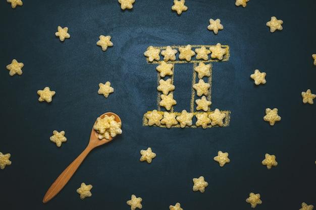 Widok z góry płasko leżał znak horoskopu gemini wykonany z chrupiących gwiazd kukurydzy na czarnym