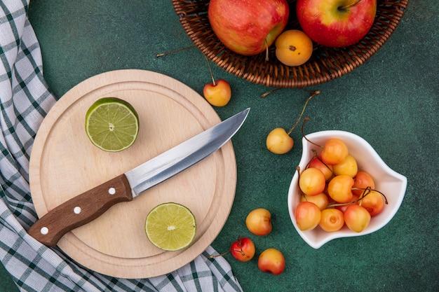 Widok z góry plasterków limonki z nożem na stojaku z białymi wiśniami i jabłkami w koszu na zielonej powierzchni
