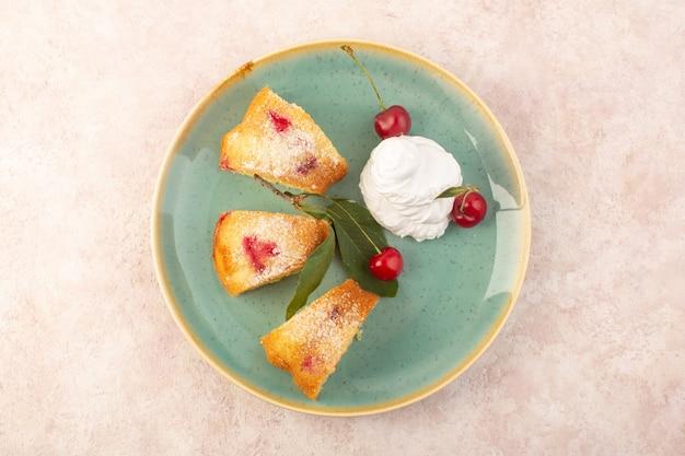 Widok z góry plastry ciasta wiśniowego pyszne wewnątrz okrągłego talerza na różowym biurku, ciastko, ciastko, ciasto cukrowe