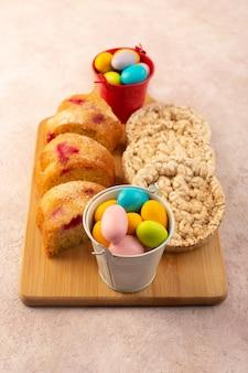 Widok z góry plastry ciasta wiśniowego z cukierkami i herbatnikami na jasnoróżowym biurku ciasto biszkoptowo-cukrowe