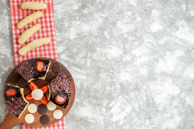 Widok z góry plastry ciasta z ciasteczkami i słodyczami na białej powierzchni
