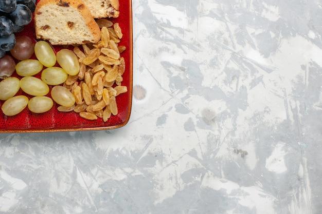Widok z góry plastry ciasta z winogronami i rodzynkami wewnątrz czerwonego talerza na jasnobiałej powierzchni