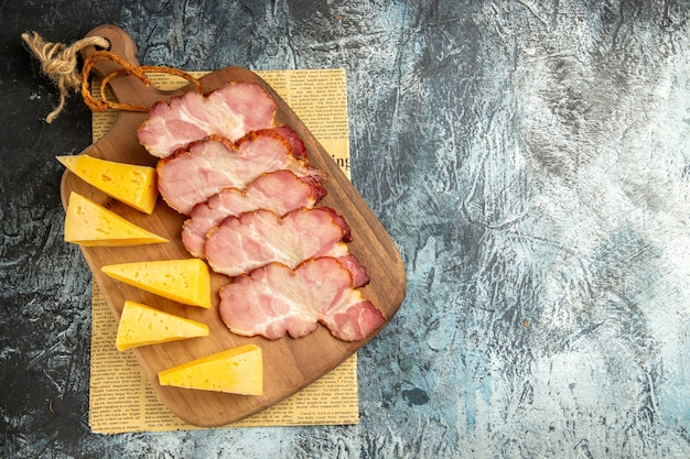 Widok z góry plastry mięsa plastry sera na desce do krojenia na gazecie na szarej powierzchni