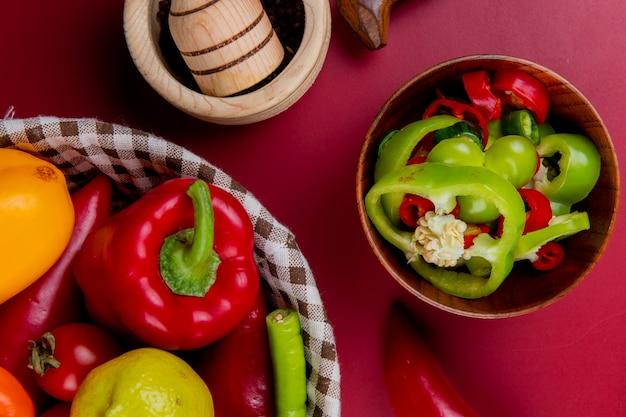 Widok z góry plastry pieprzu w misce z warzywami jak pomidor pieprzowy w koszu z kruszarką czosnku na powierzchni bordo