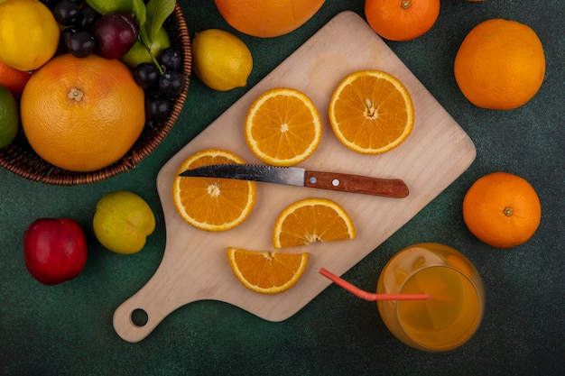 Widok z góry plastry pomarańczy na desce do krojenia z nożem grejpfrut limonka cytryna śliwka i brzoskwinia w koszu na zielonym tle