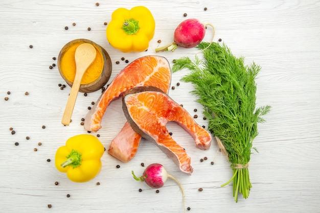 Widok z góry plastry surowego mięsa z zieleniną i papryką na białym tle