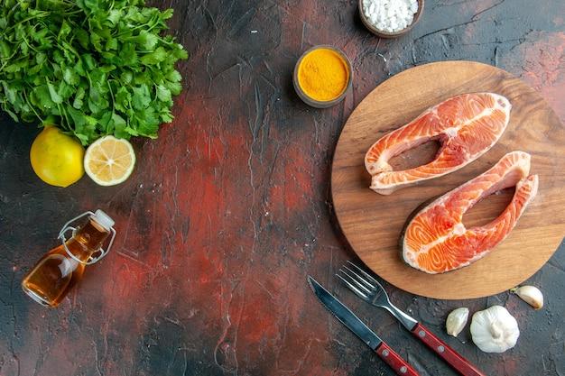 Widok z góry plastry surowego mięsa z zieleniną i przyprawami na ciemnym tle