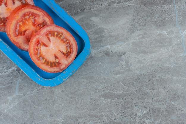 Widok z góry plastry świeżych organicznych pomidorów na drewnianym talerzu.