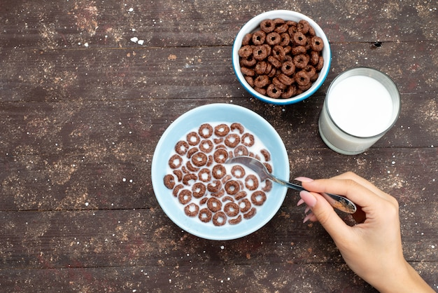 Widok z góry płatki czekoladowe z mlekiem w niebieskim talerzu i wraz z łyżką na brązowo
