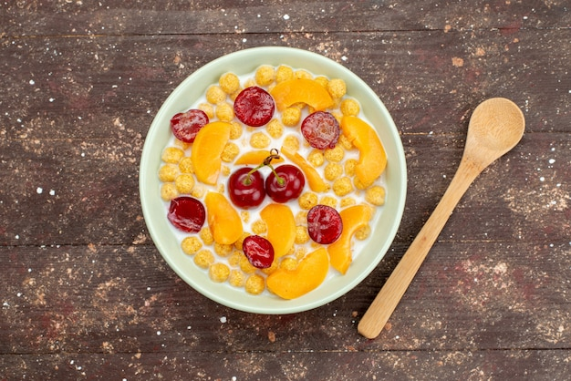 Widok z góry płatki zbożowe z mlekiem wewnątrz płyty ze świeżymi owocami na drewnie, płatki śniadaniowe płatki kukurydziane