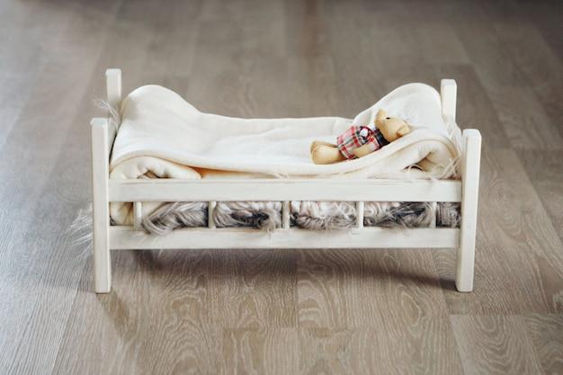Widok z góry: pluszowy miś leży w drewnianym łóżeczku. koncepcja dzieciństwa, meble dziecięce, wnętrze, wyroby z drewna
