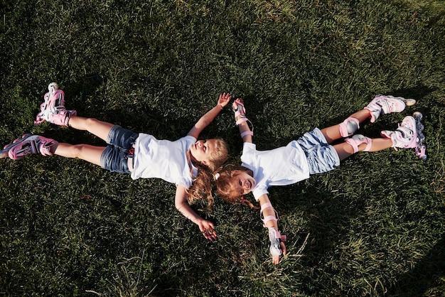 Widok z góry. poczucie wolności. dwie kobiece dzieci leżące na zielonej trawie w okresie letnim.