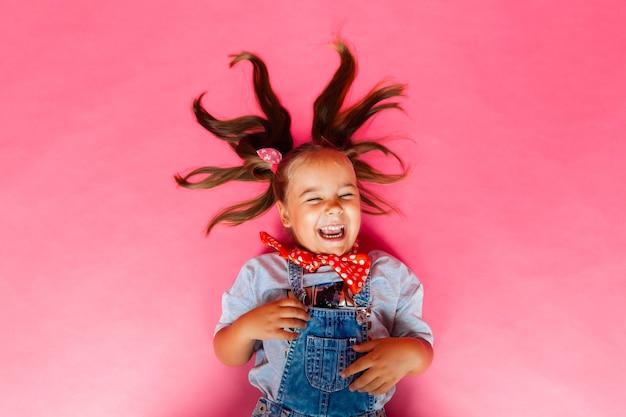 Widok z góry pod. mała dziewczynka rozpościera włosy i leży na różowym tle. koncepcja dzieci.